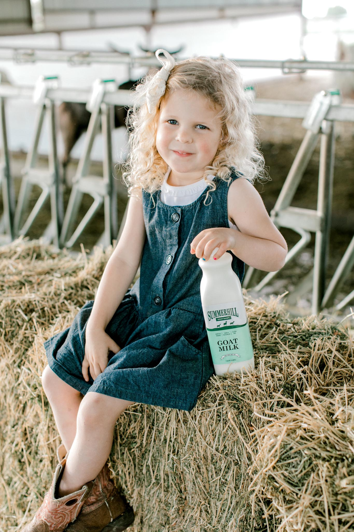 Young girl sitting on hay bale with bottle of goat milk