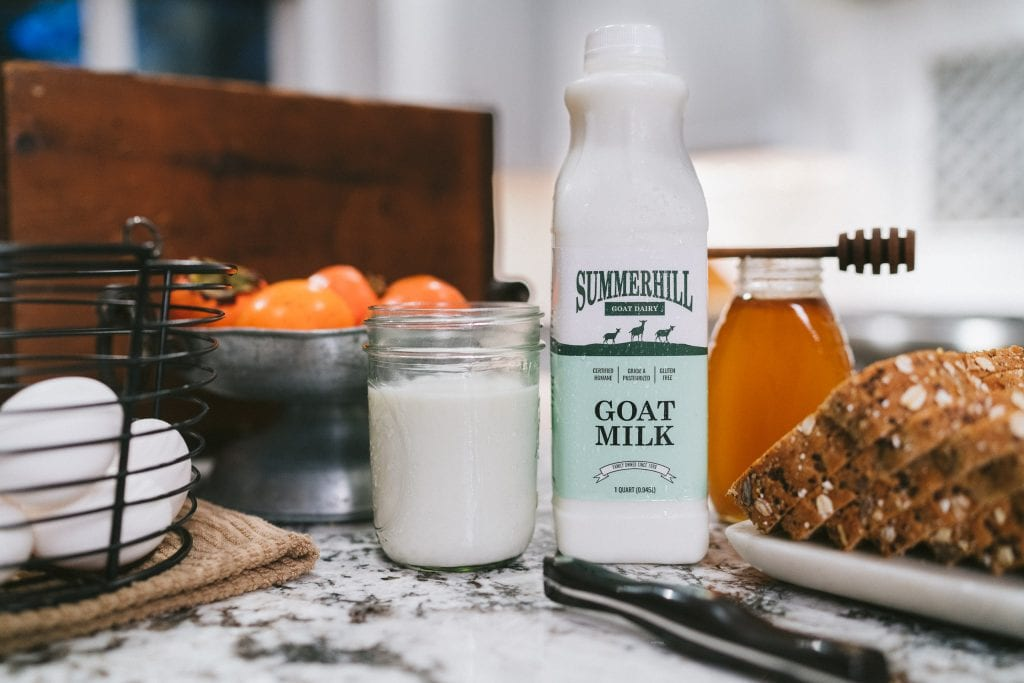 Goat milk glass with milk bottle in kitchen